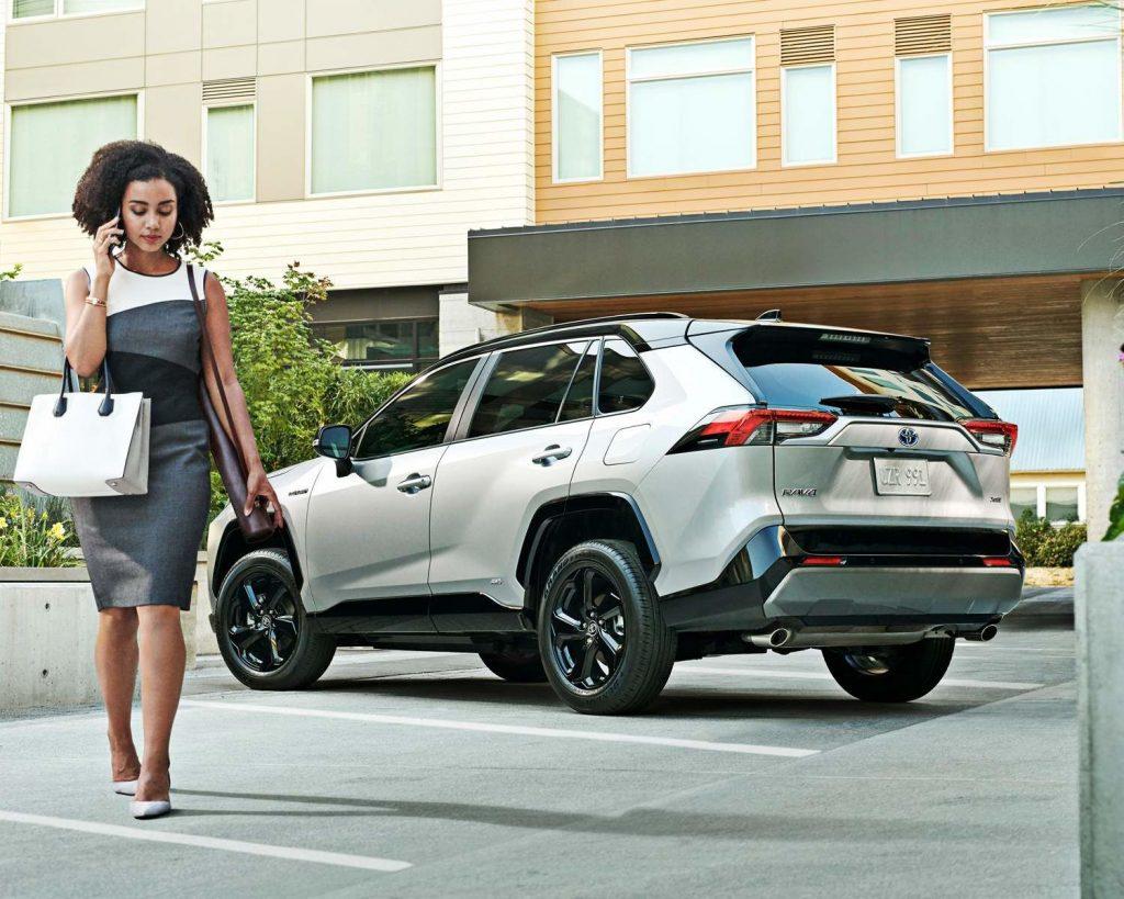 Femme d'affaire s'éloignant de sa RAV4 hybride XSE stationné de biais, légèrement de dos, en Blizzard nacré avec toit noir