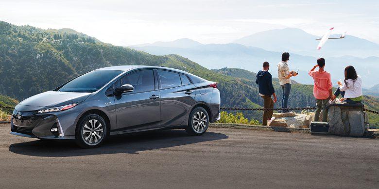 Toyota Prius devant une famille admirant des montagnes