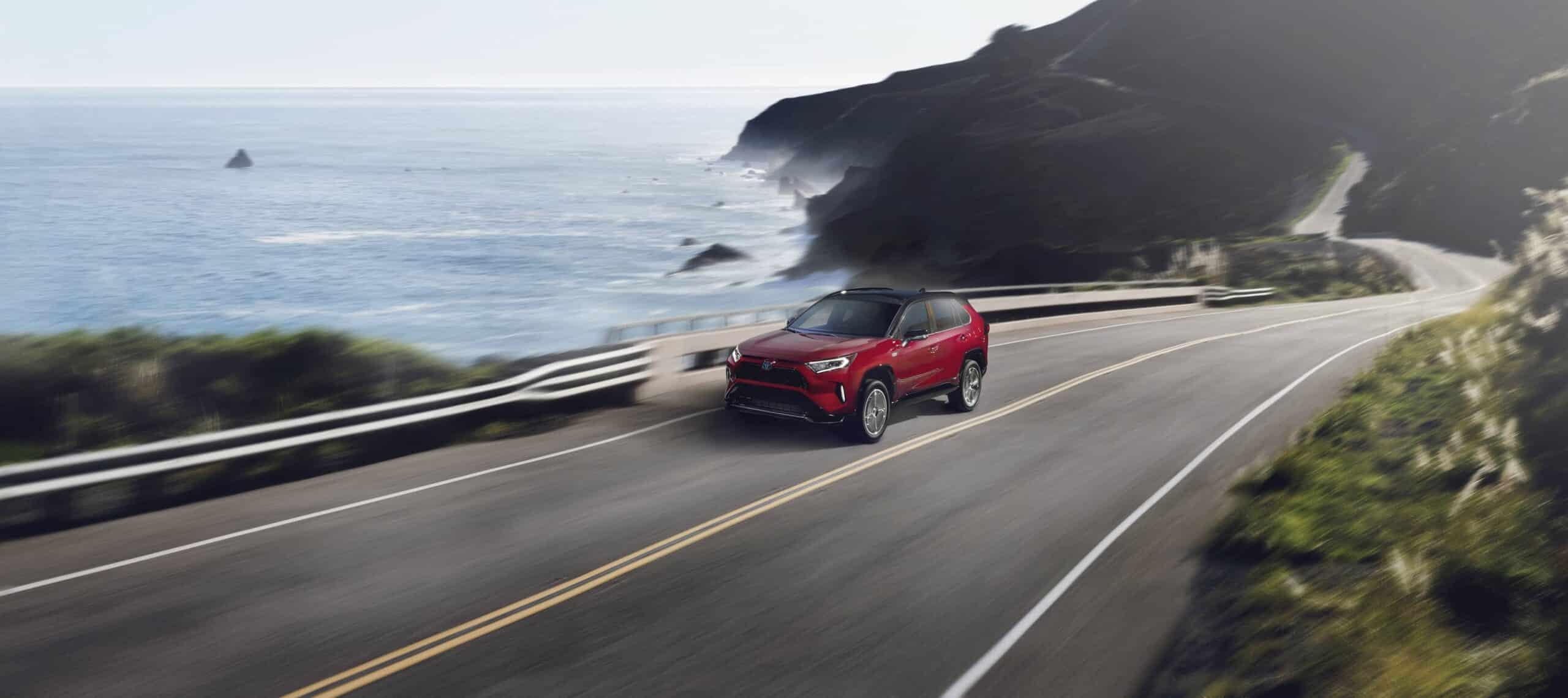 Vue avant du Toyota RAV4 Prime 2021 rouge sur une route pittoresque